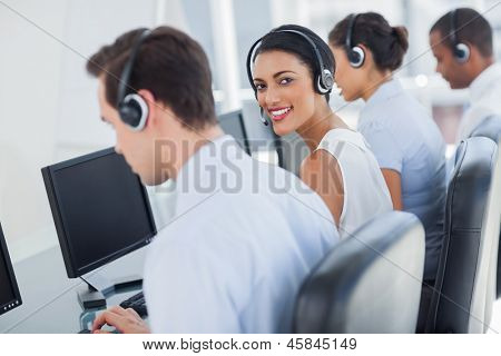 Smiling call centre employee looking over shoulder while having a discussion