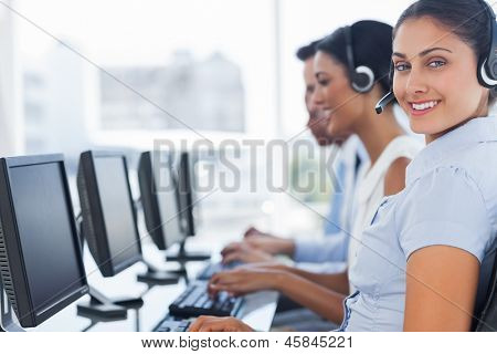 Smiling call center employee looking at camera with colleagues next to her