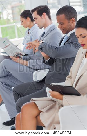 Business people sat in line in a waiting room