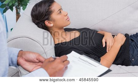 Woman lying on therapists couch as therapist is taking notes