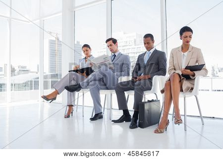 Well dressed business people sat together in a waiting room
