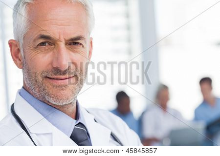 Close up of a smiling doctor sanding in front of his team