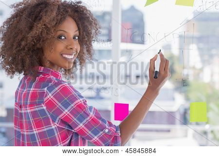 Woman drawing on flowchart with sticky notes and smiling at camera in bright office
