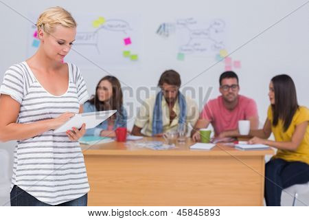 Editor using tablet pc as team works behind her at large desk