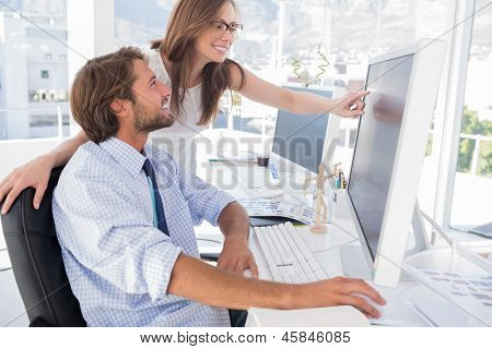 Photo editors looking at computer screen with one pointing in modern office