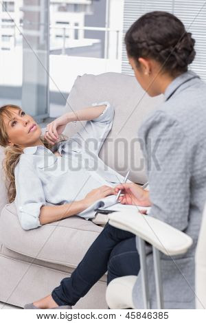 Woman lying on therapists couch looking up as therapist is taking notes