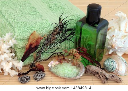 Seaweed spa accessories with green bubble bath foam and salt, towels, pumice stone and sea shells over bamboo background.