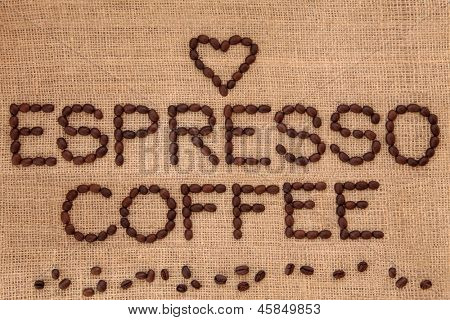 Espresso coffee bean design in word form with loose beans and heart shape over hessian background.