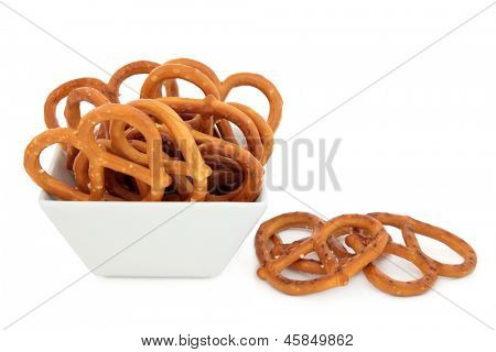 Pretzel snacks in a porcelain bowl over white background.