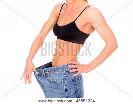 beautiful young woman with strong abs shows her old big jeans, isolated on white