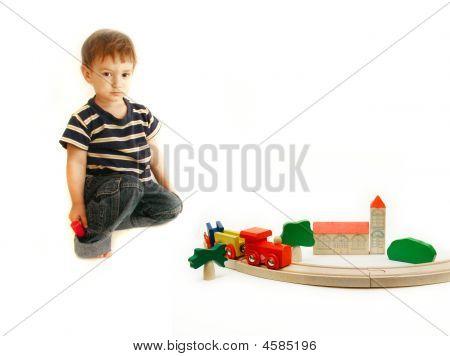 Criança brincando com trem de madeira
