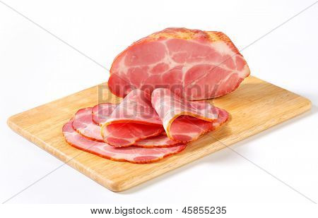 sliced block of smoked pork neck on a wooden board