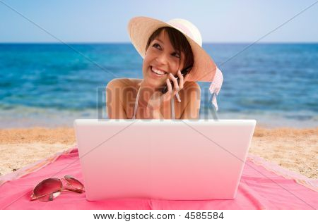 Girl Using Laptop And Mobile Speaking On The Beach