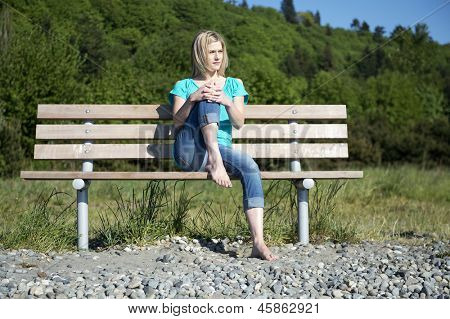 Pretty woman, sitting barefoot on a wooden bench in the park, one knee drawn up to her face, enjoying the warm spring sunlight