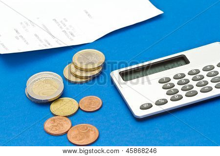 Several Euro Coins, Bill And Calculator On Blue Background