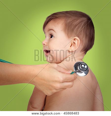 Adorable baby at the doctor's office for a pediatric examination on a green background