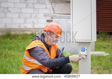 Eletricista com pasta perto de central telefônica