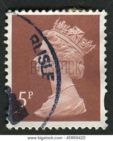 UK-CIRCA 1993: A stamp printed in UK shows image of Elizabeth II is the constitutional monarch of 16 sovereign states known as the Commonwealth realms, in dull red-brown, circa 1993.