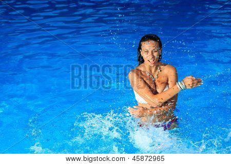 Young beautiful woman splashing water in swimming pool