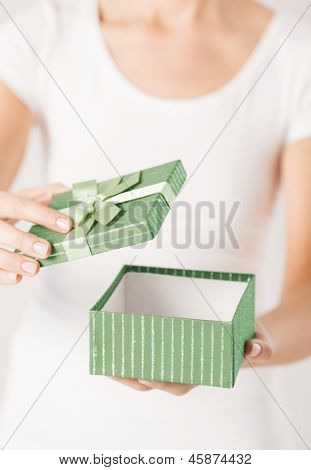 close up of woman hands opening gift box