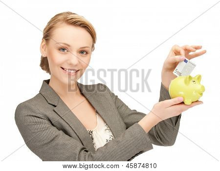 happy businesswoman putting cash money into small piggy bank