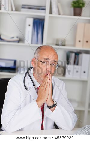 Thoughtful Doctor With Hands Clasped Sitting At Desk