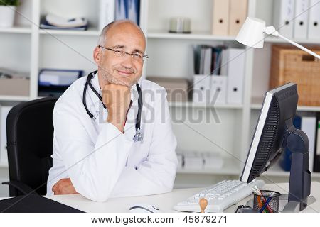 Smiling Doctor With Chin On Hand