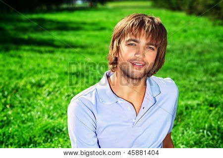 Happy smiling young man sitting on a fresh green grass.