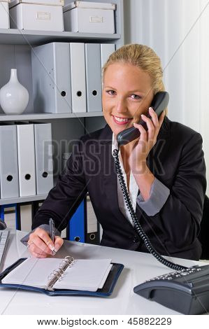 a friendly woman phone at her desk in the office and dates listed in the calendar