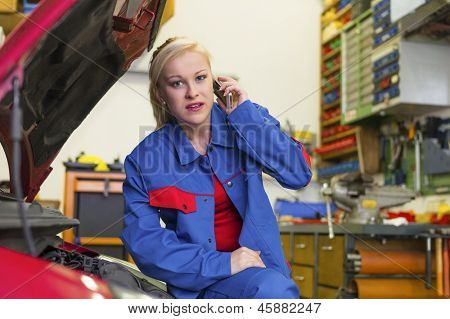 a young woman as a mechanic in a garage. rare professions for women. car is being repaired in the workshop