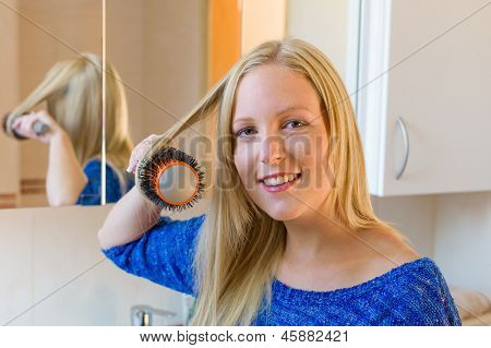 a young woman knows herself with a brush her long blond hair in the bathroom