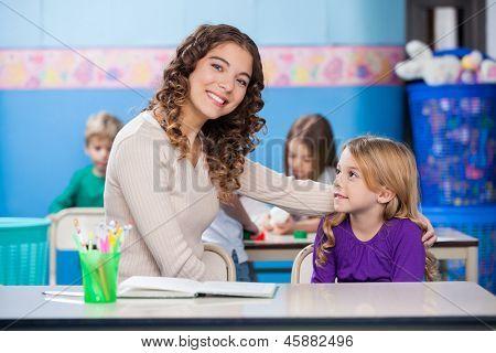 Portrait of beautiful kindergarten teacher with little girl sitting at desk in classroom