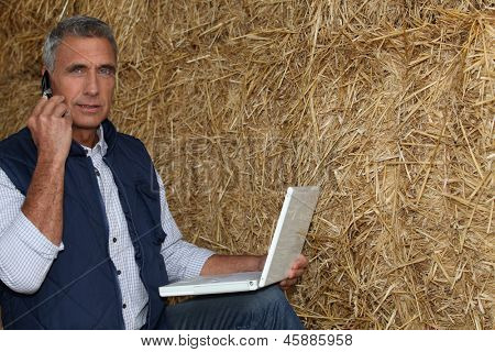 mature farmer on the phone with laptop against hay background