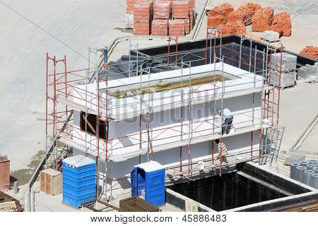 Two men color ventilation booth in large residential complex at summer sunny day.