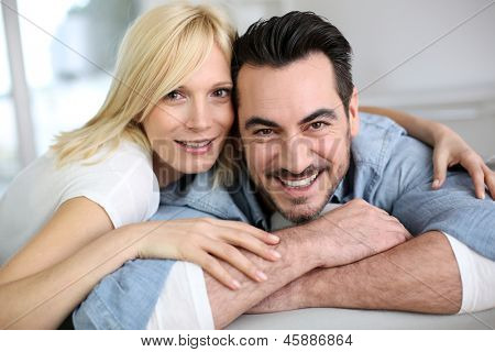 Sweet middle-aged couple embracing in sofa