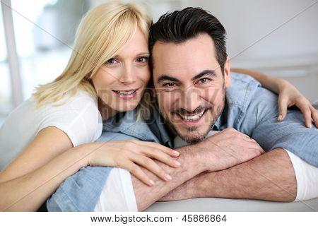 Doce casal de meia-idade, abraçando no sofá