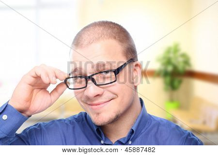 Young  attractive man  smiling in black eyeglasses in  office interior.