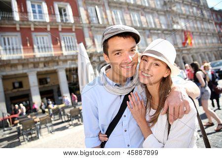 In love couple visiting la Plaza Mayor de Madrid