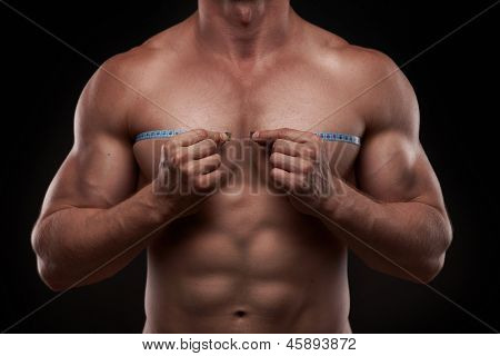 bodybuilder with a measuring tape around his chest