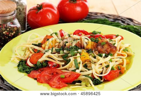 Noodles with vegetables on plates on wooden background close-up