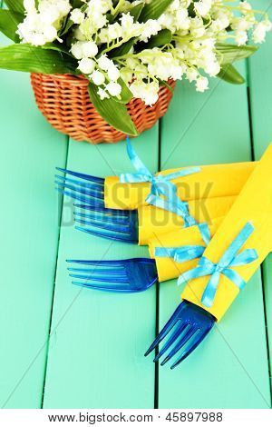 Blue plastic forks wrapped in yellow paper napkins, on color wooden background