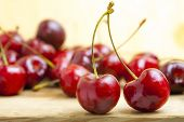 stock photo of dessert plate  - fresh red cherries on a wooden table - JPG