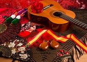 stock photo of gypsy  - Classic spanish guitar with flamenco elements as comb fan and castanets - JPG