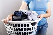 stock photo of laundry  - Casually dressed woman in blue shirt holding a basket full of dirty laundry needing washing - JPG