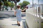 picture of girl walking away  - Little toddler girl in summer dress walking away along white fence - JPG