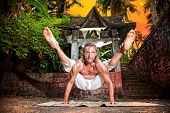 stock photo of ashtanga vinyasa yoga  - Yoga titibhasana firefly pose by fit man in white trousers near stone temple at sunset background in tropical forest - JPG