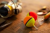 stock photo of trout fishing  - fishing reel and float on a old wooden desk - JPG