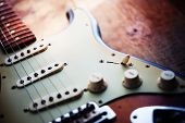 stock photo of string instrument  - Electric guitar  on a grungy old wooden surface with impressional feeling - JPG
