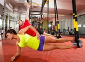 stock photo of gymnastic  - Crossfit fitness TRX training exercises at gym woman and man side push - JPG