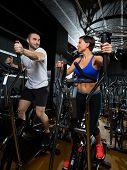 stock photo of elliptical  - elliptical walker trainer man and woman at black gym training aerobics exercise - JPG